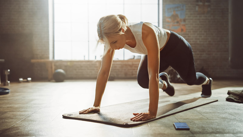 Beautiful and Young Girl Doing Running Plank Exercise on Her Fitness Mat